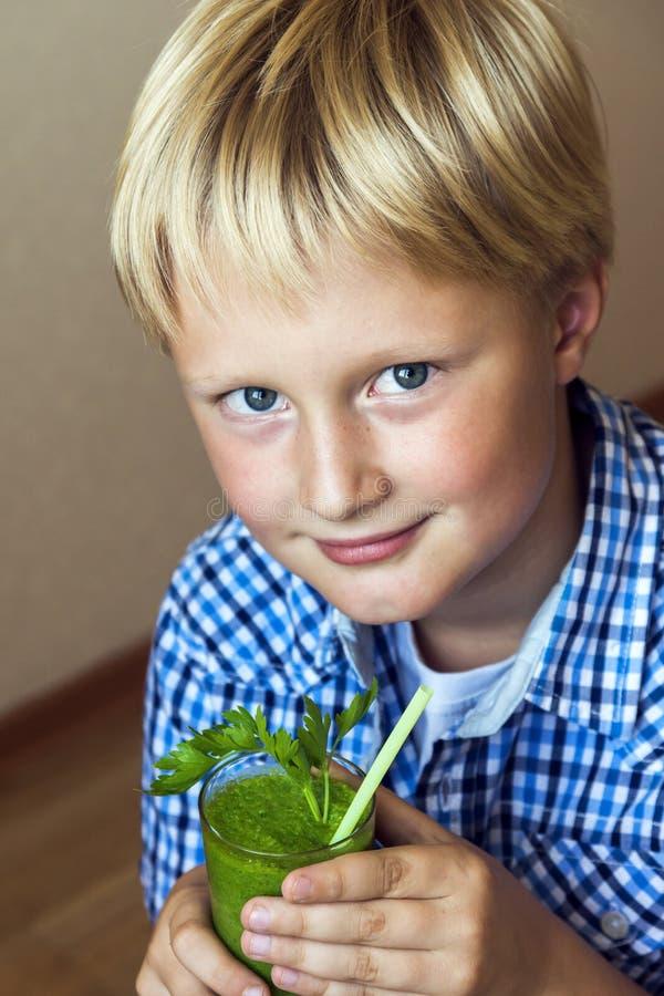Kindjongen die groene smoothie drinken royalty-vrije stock fotografie
