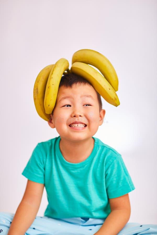 Kindjongen in een turkoois overhemd, hoofd op bananen - fruit en gezond voedsel royalty-vrije stock afbeelding