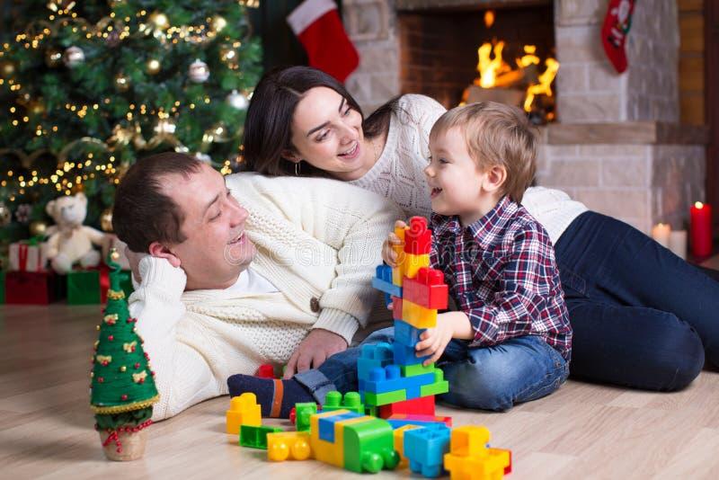 Kindjongen en zijn ouders die met blokspeelgoed onder de Kerstmisboom spelen stock foto's