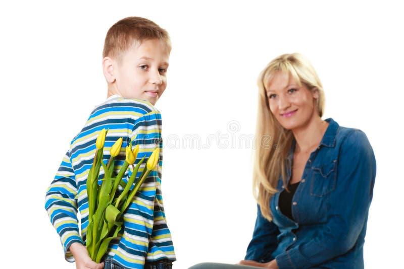 Kindjongen het geven bloeit zijn moeder stock afbeeldingen