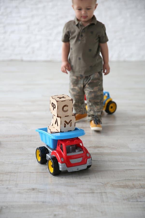 Kindjongen het spelen in de ruimte met brievenstuk speelgoed blokken stock foto's