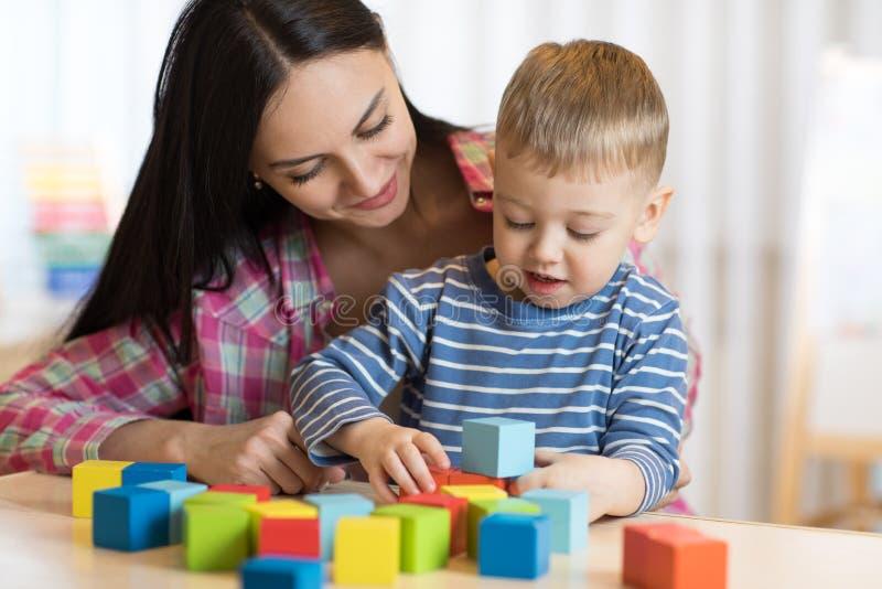 Kindjongen samen met moeder het spelen speelgoed royalty-vrije stock afbeeldingen