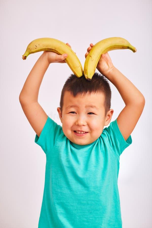 Kindjongen in turkoois bananen houden die hoornen afschilderen en overhemd die, die - vruchten en gezond voedsel glimlachen stock fotografie
