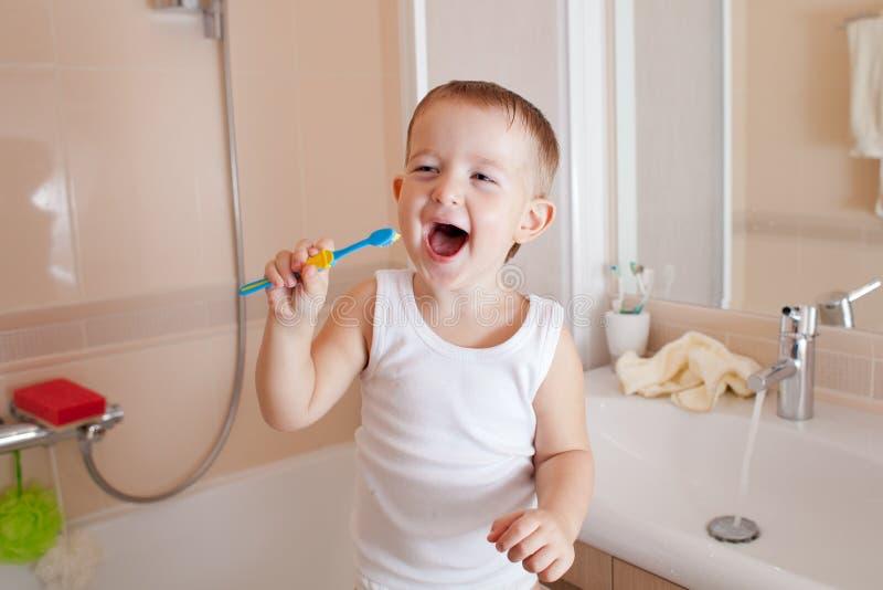 Kindjungen-Reinigungszähne im Badezimmer lizenzfreies stockbild