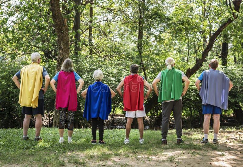 Kindliche Senioren, die Superheldkostüme tragen lizenzfreie stockfotos