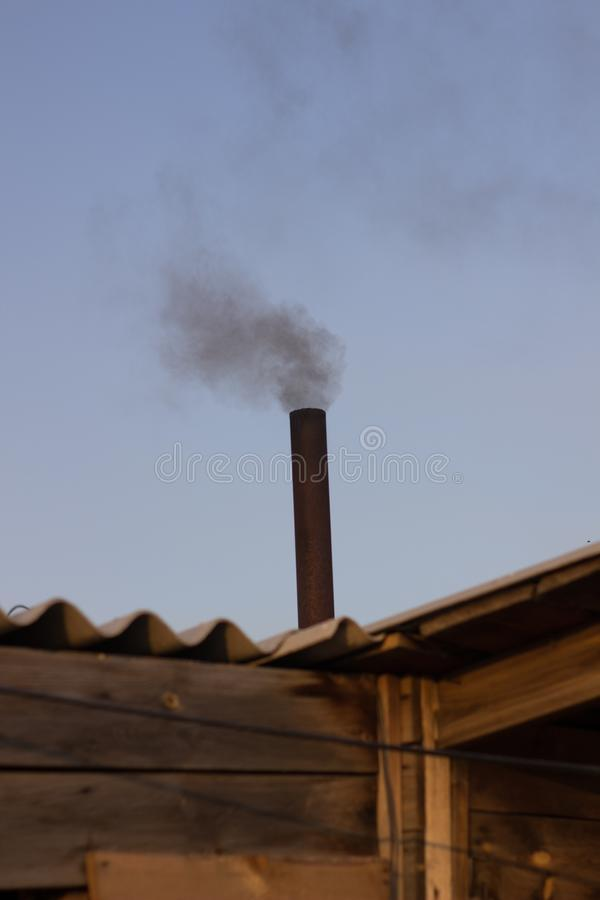 Black smoke from the chimney of the sauna royalty free stock images