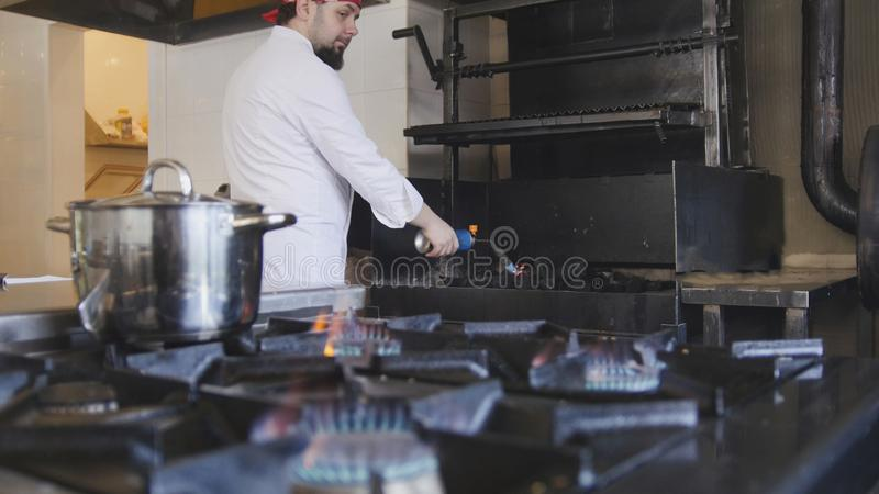 Kindling of charcoal in the barbecue oven using a gas burner slow motion stock photo