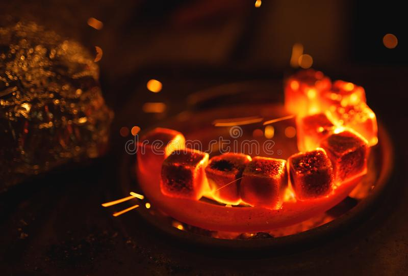 Kindling of square coal for a hookah on a special furnace with a hot spiral stock images