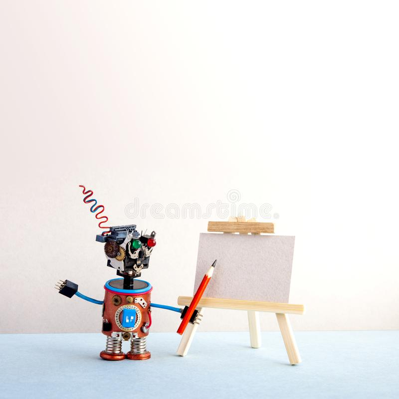 Kindly robot artist begins to create a drawing with a pencil. White paper template, wooden easel. Advertising poster. Studio school of visual arts. copy space stock photos