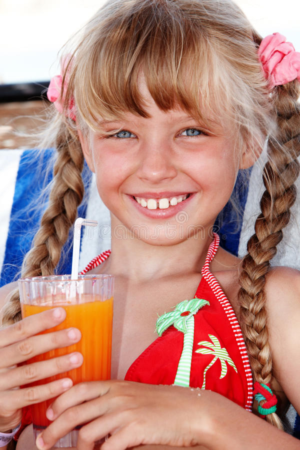 Kindmädchen im roten Bikinigetränksaft. lizenzfreies stockbild