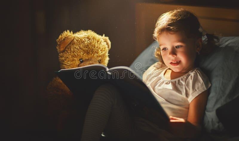 Kindmeisje die een boek in bed lezen royalty-vrije stock afbeeldingen