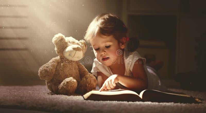 Kindmeisje die een magisch boek in donker huis lezen stock foto's