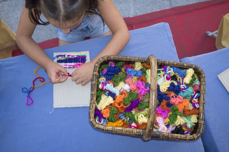 Kindmeisje die karton wevend weefgetouw leren te gebruiken royalty-vrije stock fotografie
