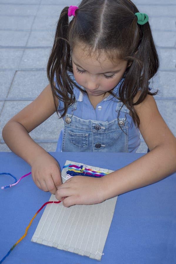 Kindmeisje die karton wevend weefgetouw leren te gebruiken stock afbeeldingen