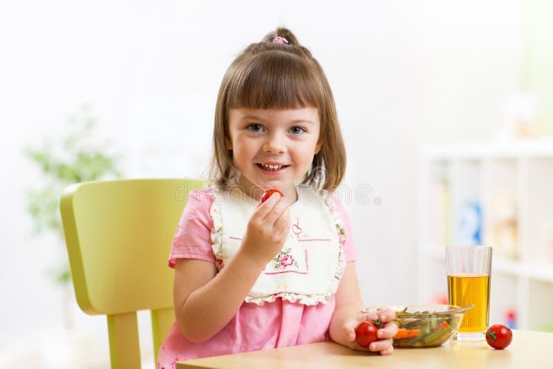 Kindmeisje die plantaardige salade in huis eten royalty-vrije stock foto
