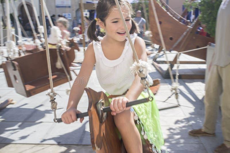 Kindmeisje die pret hebben bij Menselijke aangedreven carrousel stock foto's