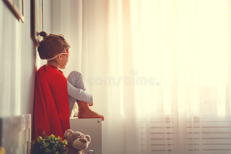 Kindmeisje in een super heldenkostuum met masker en rode mantel stock afbeelding