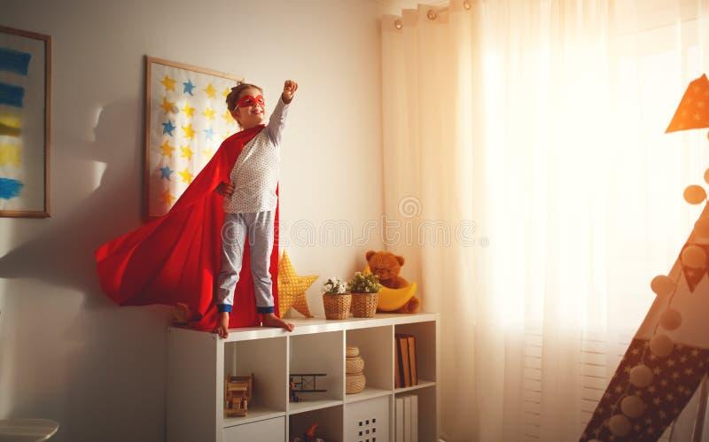 Kindmeisje in een super heldenkostuum met masker en rode mantel stock foto
