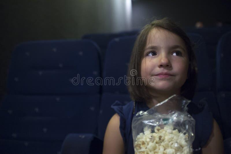 Kindmeisje het letten op film bij echte bioskoop Zij wordt gekregen een rente e stock foto