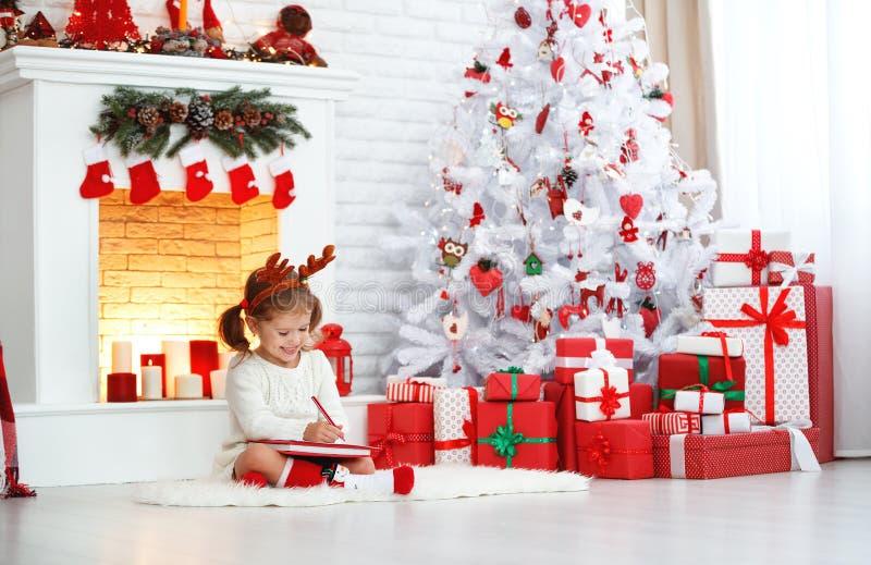 Kindmeisje het schrijven het huis van brievensanta dichtbij Kerstboom royalty-vrije stock fotografie