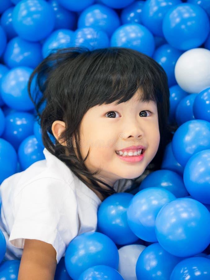 Kindmeisje het spelen in de balpool stock foto's