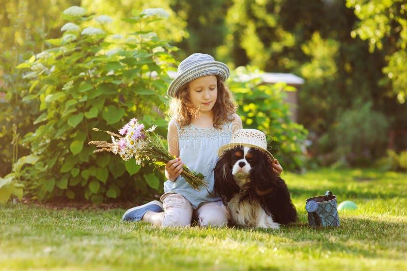 kindmeisje het spelen met haar spanielhond in de zomertuin, allebei die grappige tuinmanhoeden dragen stock foto