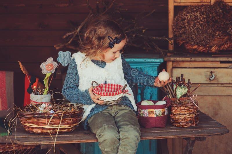 Kindmeisje het spelen met paaseieren en met de hand gemaakte decoratie in comfortabel buitenhuis stock afbeeldingen