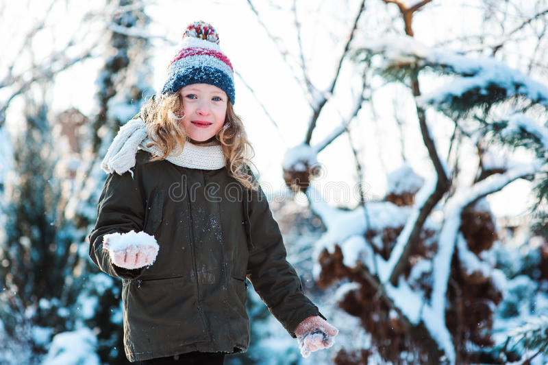 Kindmeisje het spelen met sneeuw wintergarden binnen of bos, makend sneeuwballen en blazend sneeuwvlokken stock foto