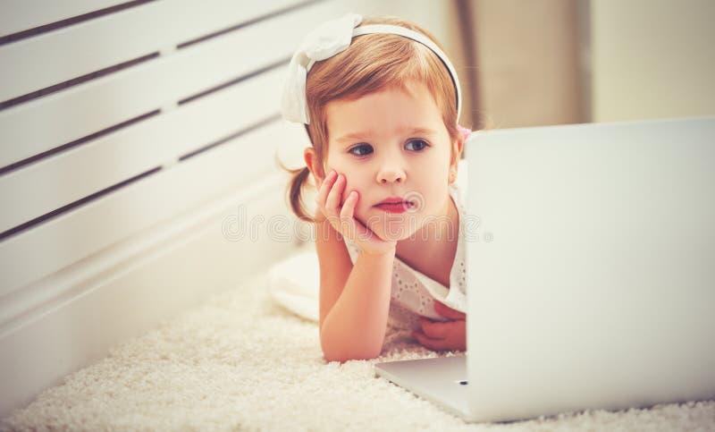 Kindmeisje met een laptop computer royalty-vrije stock foto