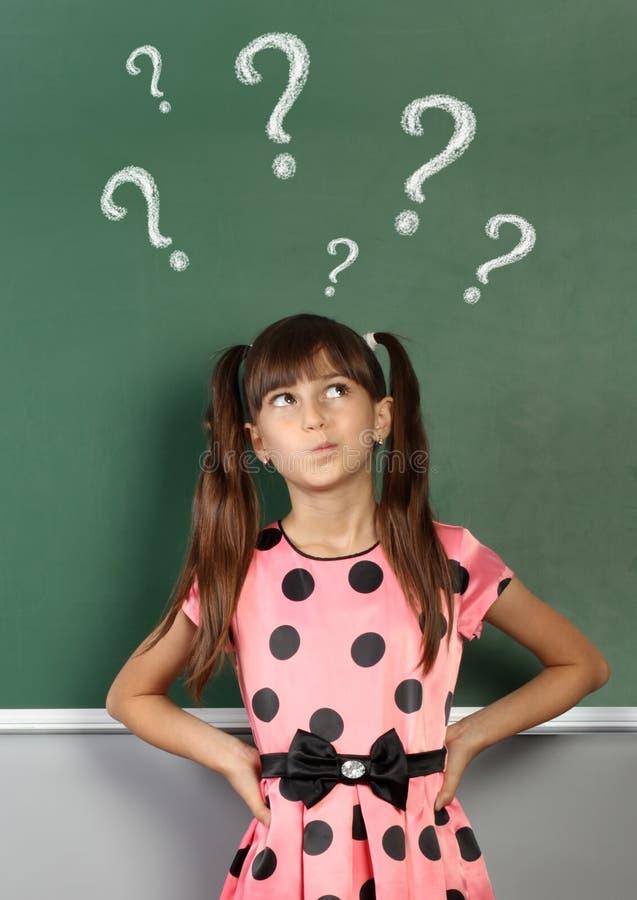 Kindmeisje met vraagteken op schoolbord stock foto