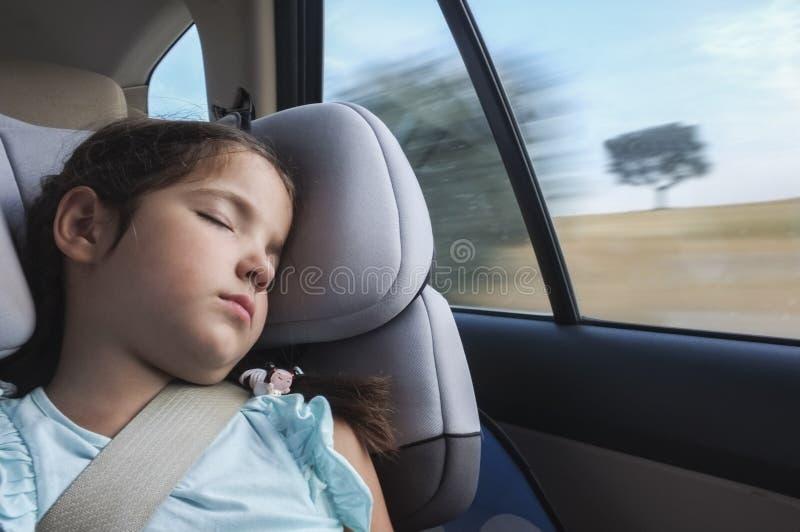 Kindmeisje in slaap in een zetel van de kindveiligheid in een auto stock afbeeldingen