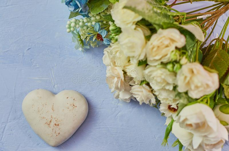 Kindness, love. Delicate blue background with white chocolate heart cookies and a bouquet of flowers on a blue background stock photo