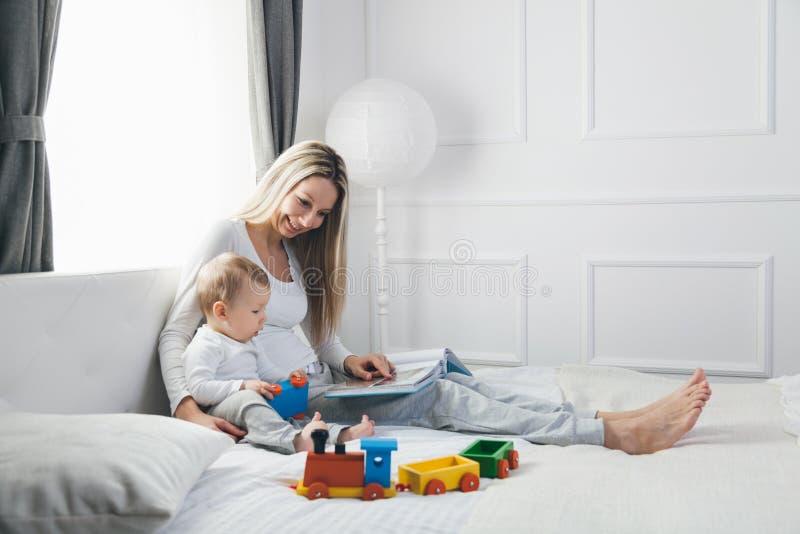 Kindonderwijs Gelukkige moeder met haar peuterzitting op het bed en lezing een boek royalty-vrije stock afbeelding