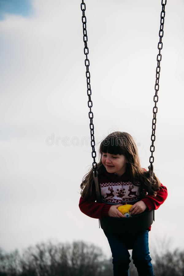 Kindschommeling op een reeks van de parkschommeling stock foto