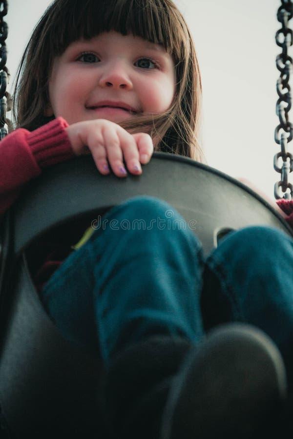 Kindschommeling op een reeks van de parkschommeling stock afbeelding