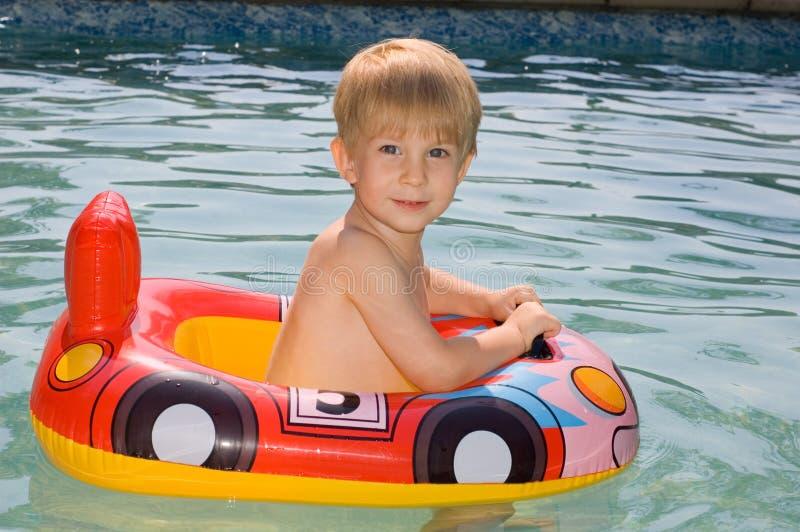 Kindschwimmen in einem Swimmingpool stockfoto