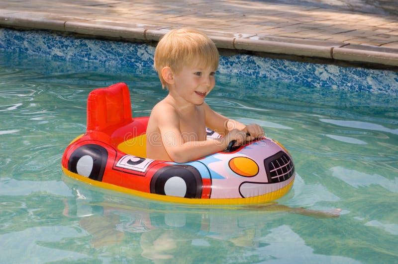 Kindschwimmen in einem Swimmingpool lizenzfreies stockbild