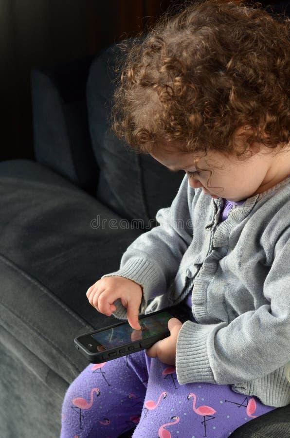 Kindspel op mobiele telefoon stock afbeelding