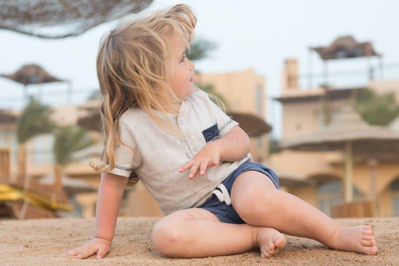Kindspel op zand De kleine jongen zit op tropisch strand De zomeractiviteit op strand De vakantie, vrije tijd en ontspant concept royalty-vrije stock foto