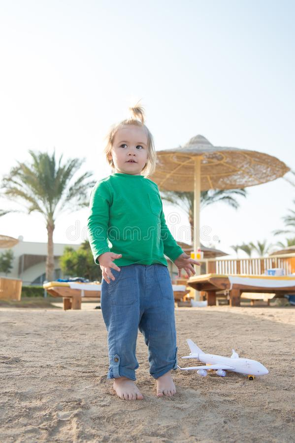 Kindspel op zandstrand Kleine jongen met vliegtuigstuk speelgoed openlucht Het jonge geitje heeft pret op de zomervakantie Verbee royalty-vrije stock foto