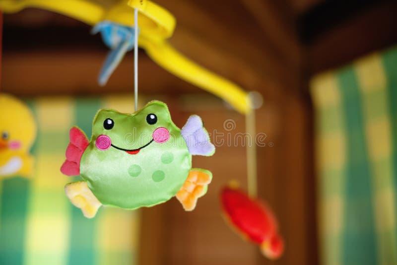 Kindstuk speelgoed met kikker het hangen op babywieg stock foto's