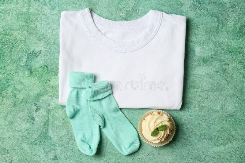 Kindt-shirt met cupcake en sokken op kleurenachtergrond stock afbeeldingen