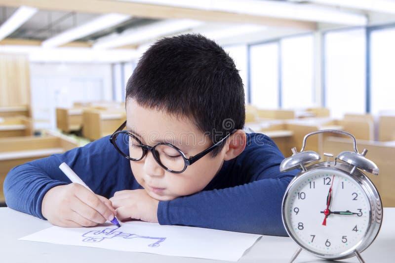 Kindtekening in klasse met een klok op bureau stock fotografie