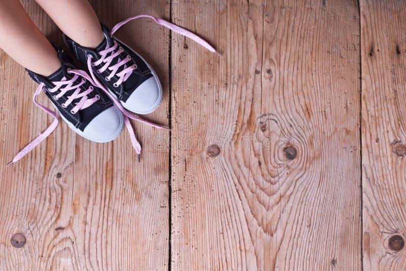 Kindvoeten in tennisschoenen op oude houten vloer royalty-vrije stock afbeelding