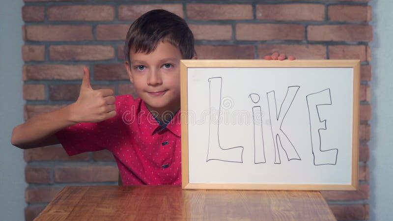 Kindzitting bij de bureauholding flipchart met het van letters voorzien als royalty-vrije stock foto's