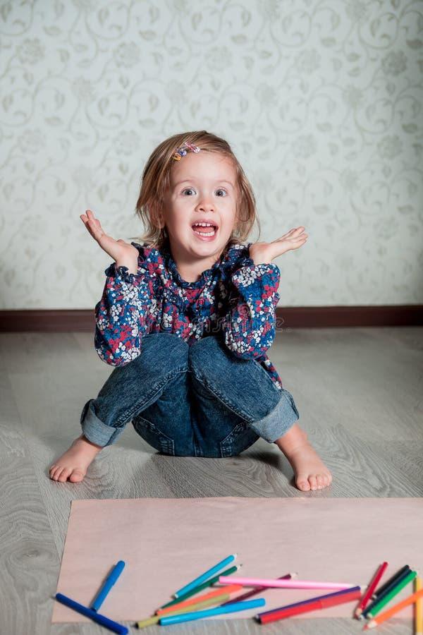 Kindzitting op de vloer dichtbij kleurpotloden en document Meisjetekening, het schilderen Het concept van de creativiteit wow oop stock fotografie