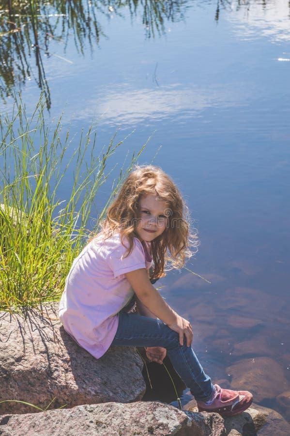Kindzitting op een rots dichtbij het water royalty-vrije stock foto