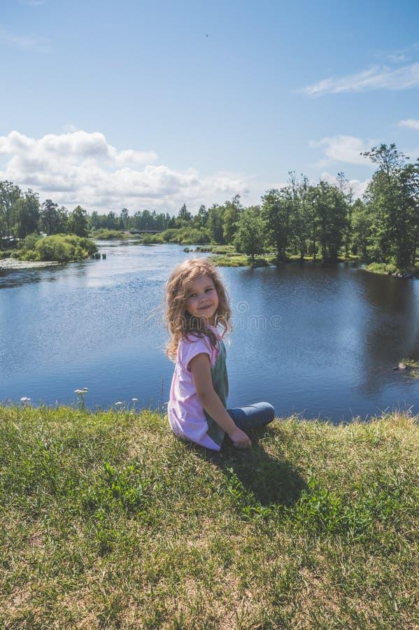 Kindzitting op een rots dichtbij het water royalty-vrije stock foto's