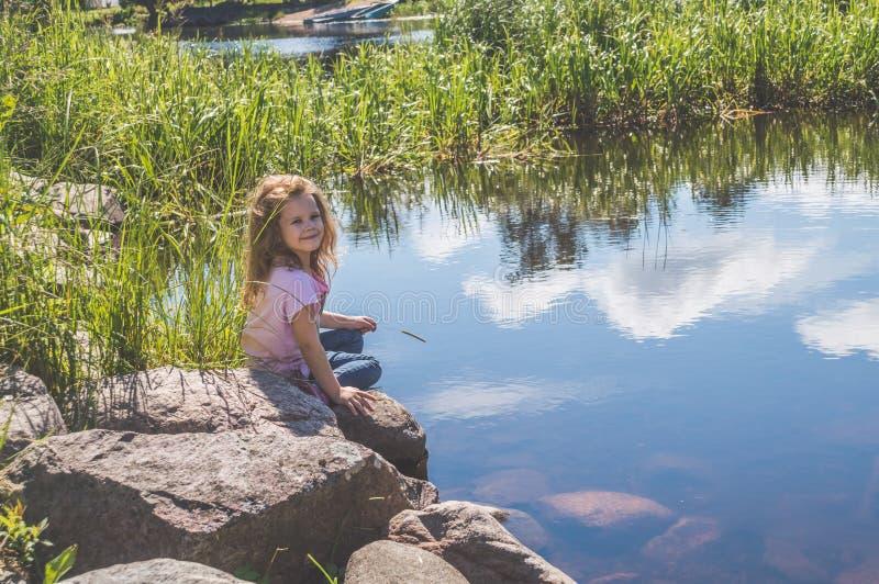 Kindzitting op een rots dichtbij het water royalty-vrije stock fotografie