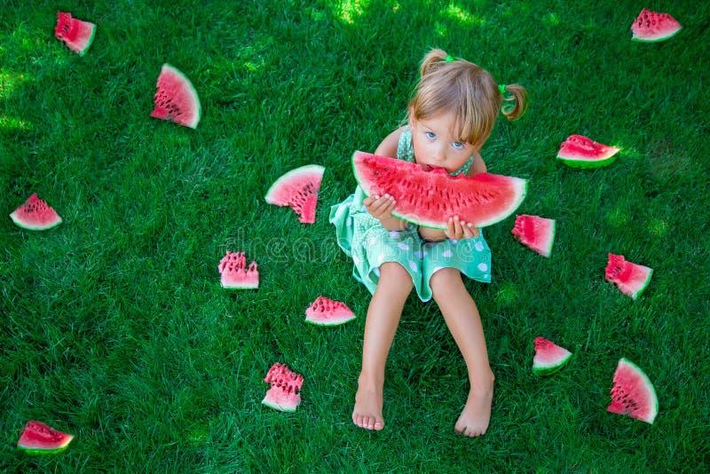Kindzitting op het gras en het eten van plak van watermeloen in de zomer het bekijken camera De ruimte van het exemplaar royalty-vrije stock afbeeldingen